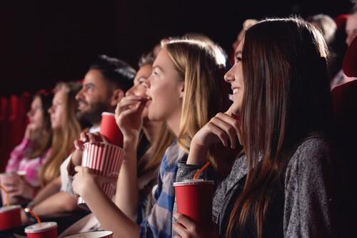 groupe d'amis absorbé par le film au cinéma