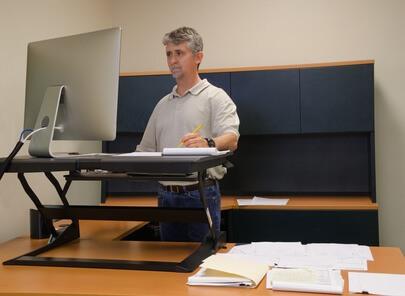 Travailler debout sur ordinateur avec un bureau ajustable